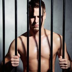 Sexy man behind iron prison bars