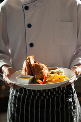 german pork, a chef uniform holding a dish of german pork leg