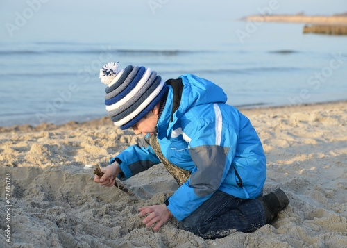 Kind in Winterkleidung spielt am Strand