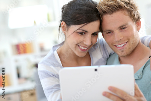 Young couple in sofa websurfing on internet with tablet