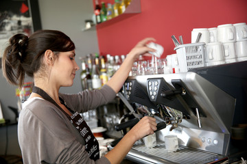 Waitress serving coffee from machine