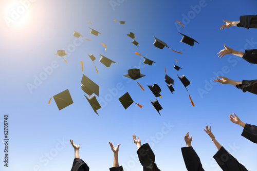 happy young graduates throwing hats