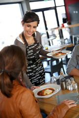 Cheerful young waitress serving lasagna to customers