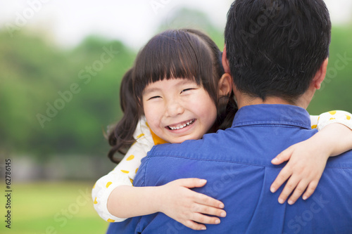 happy little girl hugging embracing her father
