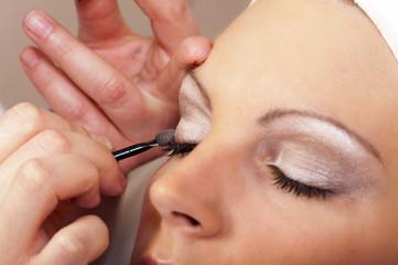 Kosmetikerin beim Makeup der Augenlider
