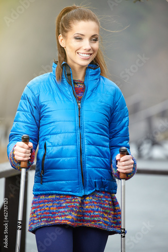 Closeup of young woman with Nordic walking poles in spring villa