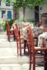 Cafe tables and chairs outside, Athens, Greece.Toned vintage pho