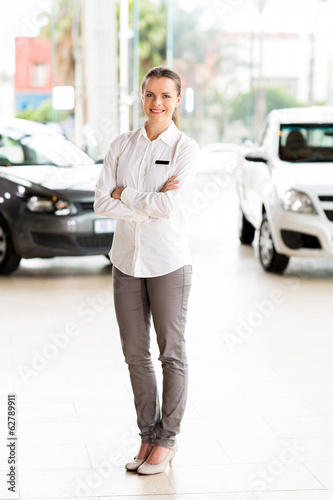 saleswoman standing at car dealership