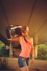 Hip hop woman with a cap which holding a tape recorder on should