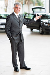 car salesman doing welcoming gesture