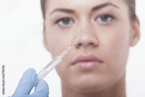 model on white background having botox injection