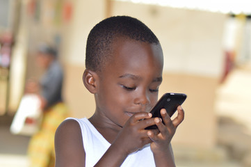 un enfant manipulant le tactile d'un téléphone mobile