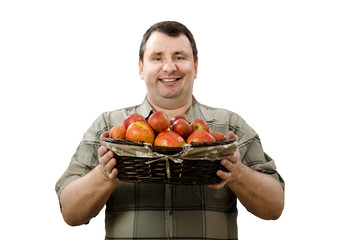 Happy farmer holding a basket of ripe red apples