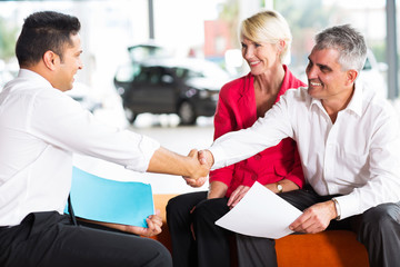 car salesman handshaking with buyer
