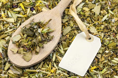 Curative natural herbal tea with hang tag on wooden spoon