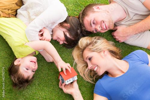 Familie liegt auf der wiese mit haus in der hand - 62792754