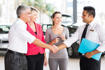 middle aged man handshake with car salesman