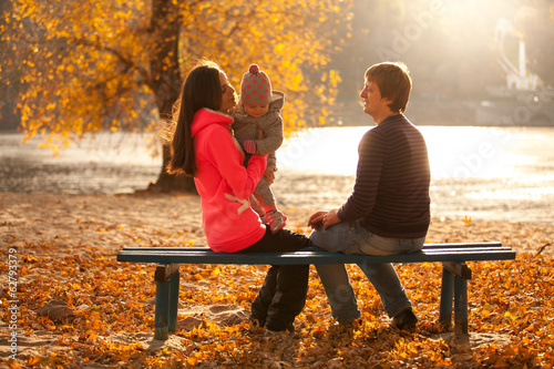 Young family having fun at autumn park on bench near river
