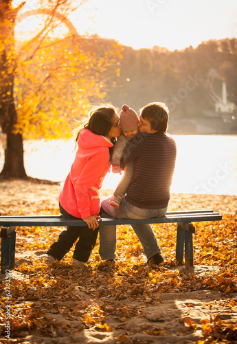 Young family sitting with small daughter on bench at lake