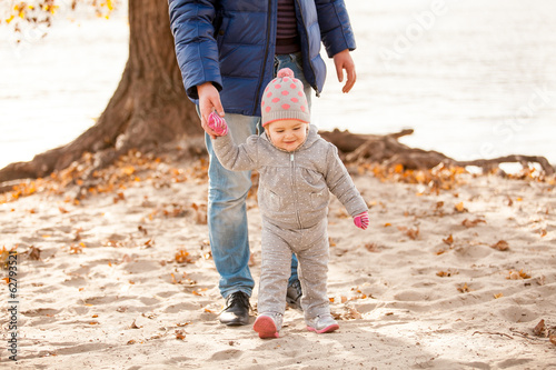 Young man walking on beach with little girl