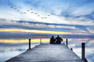 gente en el embarcadero esperando el amanecer