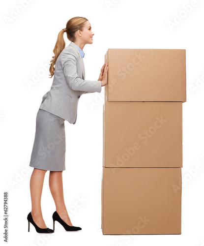 smiling businesswoman pushing tower of cardboards
