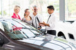 vehicle salesman showing new car to family