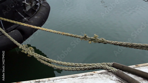 A rope tied on the ship on dock