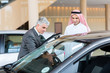middle aged car dealer showing new car to Arabian buyer