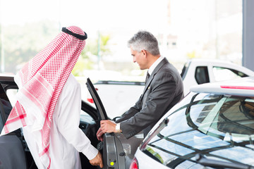 Arabian man getting in a new car for test drive