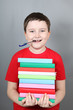 Boy with a pen in his mouth holding a stack of books