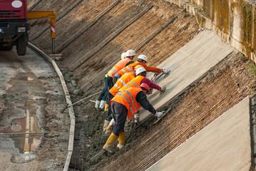Operai a lavoro, cantiere rifacimento argini cemento