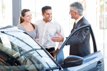 mature salesman showing new car to a couple