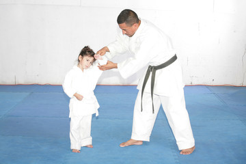Black belt Karate teaching a little girl