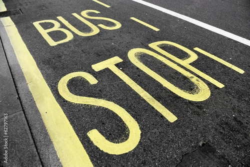 Bus stop sign on asphalt