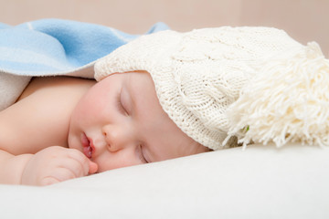 Cute sleeping baby in knitted hat with pompom