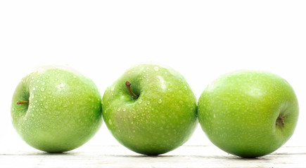three granny smith apple over white