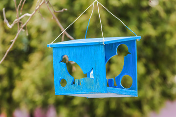 wooden bird feeder with silhouettes of birds