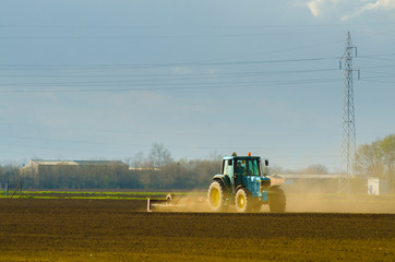 Blue tractor working on thre agricultural field