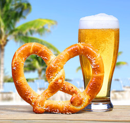 Beer Glass with German Pretzel over Beach View with Palms