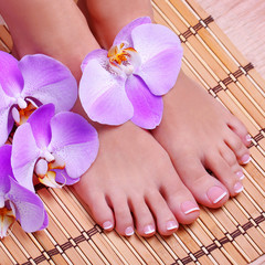 Pedicure with pink orchid flowers on bamboo mat. Beautiful femal
