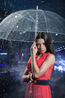 Young pretty woman with umbrella under rain on a dark background