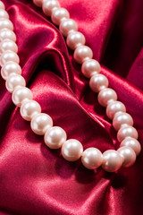 Pearl necklace on red satin background