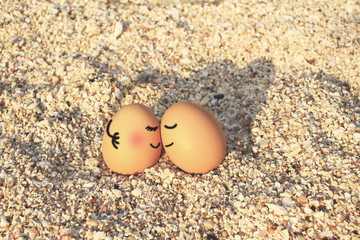 Happy lover eggs sitting on beach with vintage filtered effect