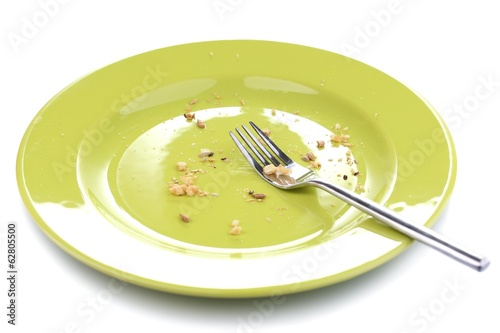 Plate with crumbs and used fork and knife, close-up,
