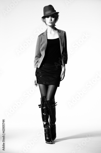 Fashion portrait of beautiful woman with hat walking in studio,