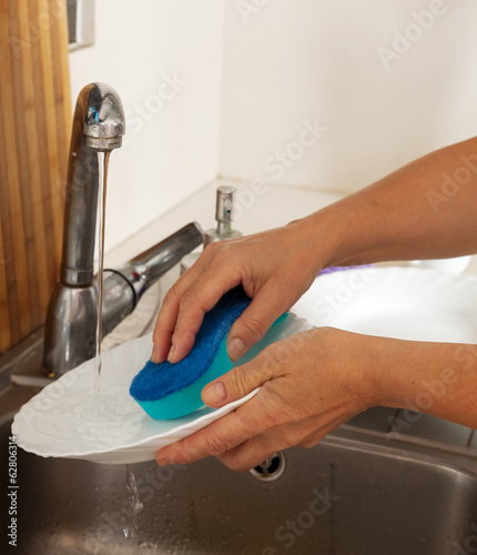Woman's hands washing plates
