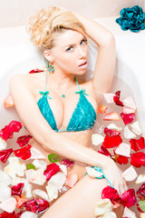 blond woman in bath with rose petals