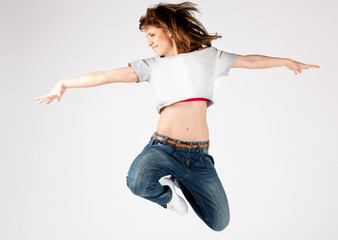 Beautiful young woman jumping on a light background