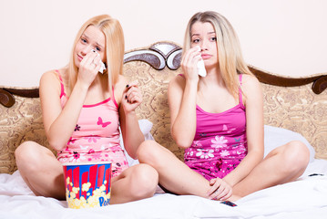 Two blond women in bed with popcorn watching movie and crying